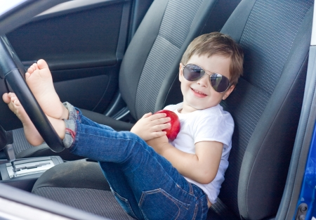 window shades: Boy with glasses and red apple sitting in car