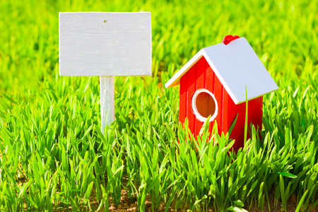 Red house and signboard on grass photo