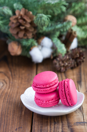 Pink macaroons with christmas decorations on woooden background Stock Photo