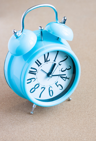 Blue alarm clock on cork background