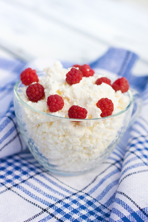Milk and glass bowl with soft cheese and raspberry