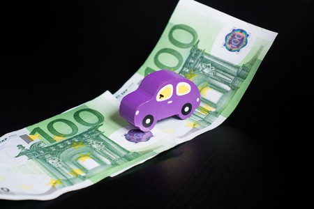 Toy car and euros on black background Imagens