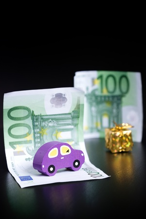Toy car, euros and golden present on black background