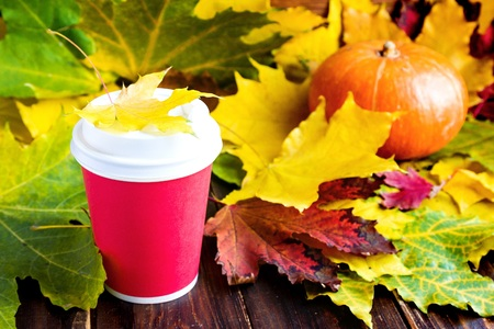 Red Coffee to go cup witn marple leaf and pumpkin on wood Imagens