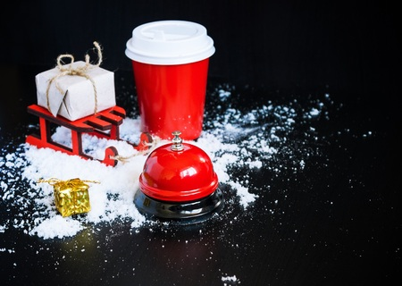 Coffee to go in red cup, sledge, bell call and present on black