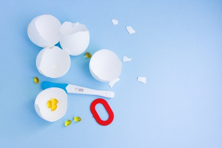 Infertility. Negative pregnancy test, pills, eggshell and number zero on blue background