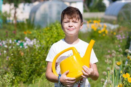 Süßer Junge mit Gießkanne im Garten im Sommer Standard-Bild
