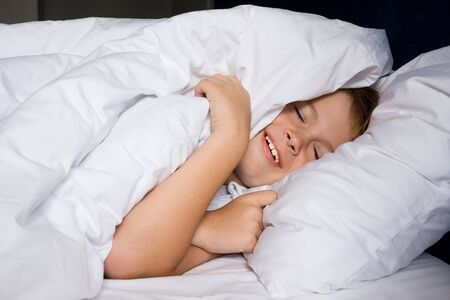 Smiling young boy lies in bedroom and smiles Foto de archivo