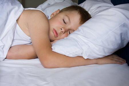 Tired young boy sleeping in bedroom Foto de archivo