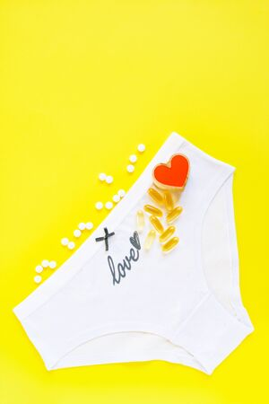 Female white panties with grew bow and word love, heart and pills on yellow background. Gynecology. Health care, contraception, planned pregnancy. Copy space