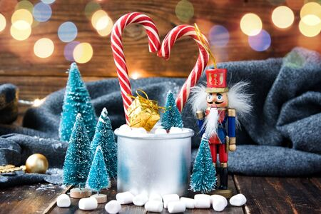 Christmas marshmallows, nutcracker and new year decorations on wood with grey plaid. Winter holidays Stock Photo