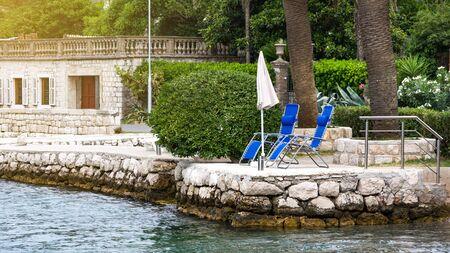 Beach chairs and umbrella at waterfront. Boko Bay in Kotor, Montenegro Stock Photo