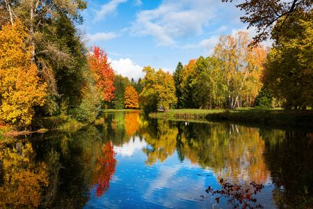 Autumn foliage in Pavlovsky park, Pavlovsk, Saint Petersburg, Russia. Autumn park with pond. Sky is reflected in water. Archivio Fotografico