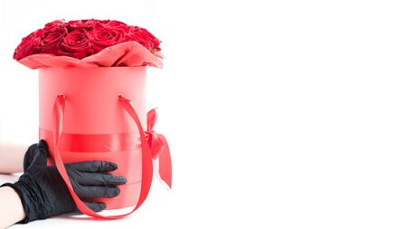 Hands in black medical gloves with red roses in paper box. Contactless flower delivery during isolation during coronavirus pandemic