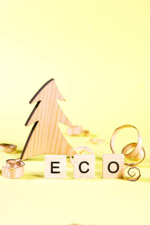 Wooden fur-tree, curled shavings and word eco on yellow. Eco toys. Save the forests, awareness concept. Environmentally friendly investments. Sawdust of woodworking industry