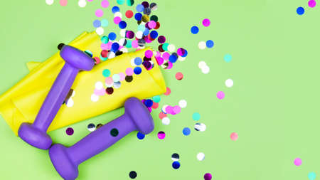 Holiday fitness. Healthy and active lifestyles greeting card concept. Purple dumbbells, yellow rubber band and confetti Stock Photo