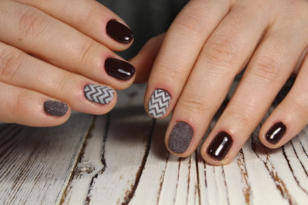 fashionable brown manicure female hands on long nails