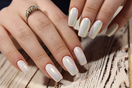 fashionable white manicure of nails on a beautiful textural background