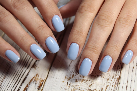 stylish blue manicure with a design on beautiful hands