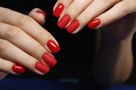 beautiful red manicure of nails on the background of fashionable texture