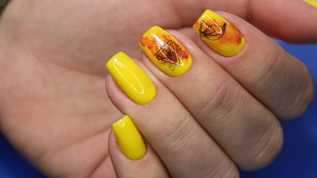 Beautiful yellow manicure on trendy textural background. Reklamní fotografie