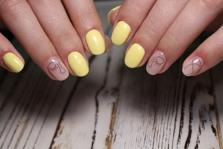 Fashionable yellow manicure on beautiful female hands Reklamní fotografie