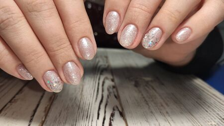 Closeup photo of a beautiful female hands with elegant manicure and diamond rings.