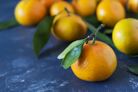 raw: Mandarins with leaves close-up on a blue background. Horizontal photo.