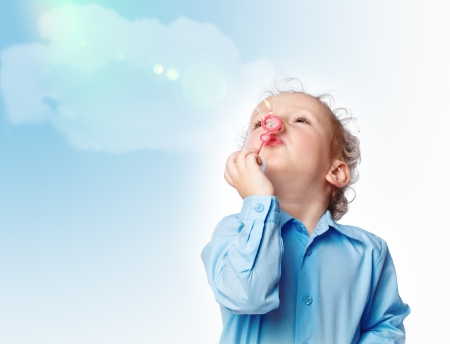 small boy blowing a bubble in the sky Stock Photo