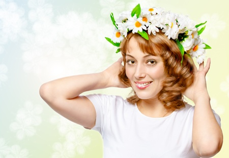 young beautiful woman in a wreath of flowers on the abstract background Stock Photo