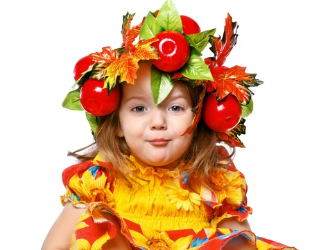 portrait of a beautiful little girl in a wreath of leaves and apples