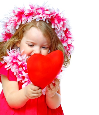 portrait of a beautiful little girl holding a heart photo