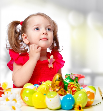 portrait of a little girl paints the eggs on a white background