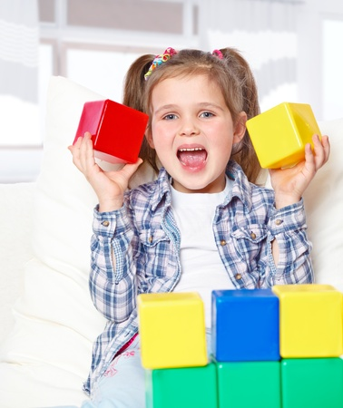 portrait of a girl playing with blocks, sitting on the couch at home Stock Photo