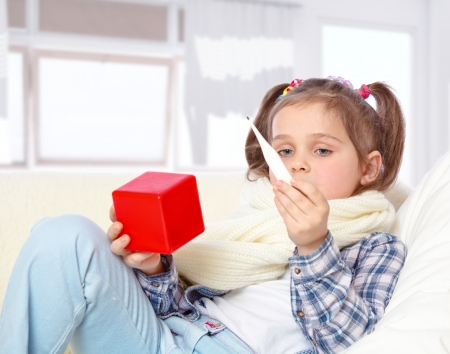 measures the temperature of a sick little girl lying on the couch Stock Photo