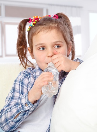 portrait of a cheerful little girl drinking water from a bottle on the abstract background Stock Photo