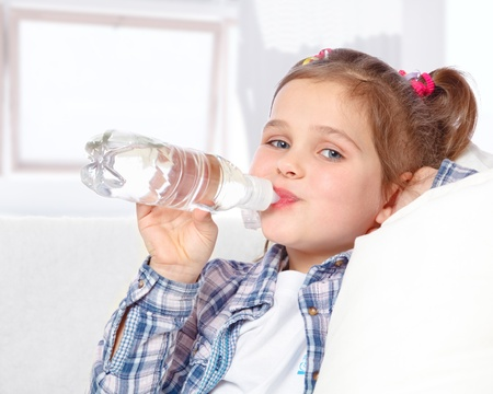 portrait of a cheerful little girl drinking water from a bottle on the abstract background Stock Photo - 17289459