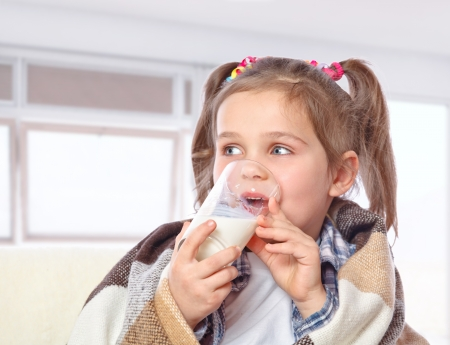 Beautiful girl drinking milk, isolated on  background Stock Photo - 17289460