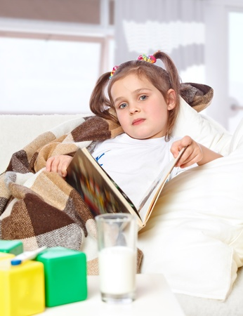 little sick girl reading a book in bed Stock Photo - 17289461