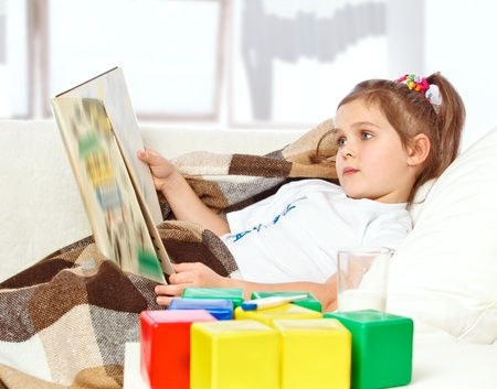 little sick girl reading a book in bed Stock Photo - 17289454