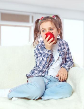 Beautiful girl eating an apple sitting on a sofa Stock Photo