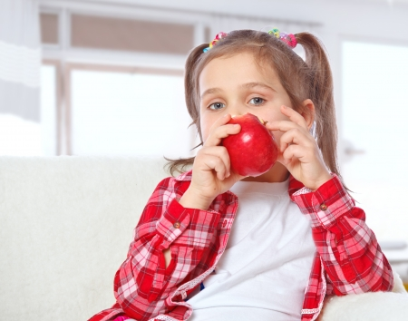 Beautiful girl eating an apple sitting on a sofa Stock Photo - 17289462