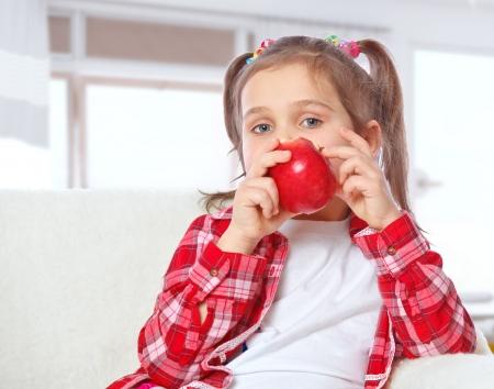 Beautiful girl eating an apple sitting on a sofa Stock Photo - 17289462