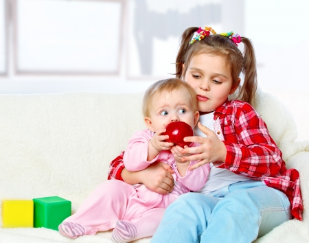 portrait of an older sister hugging her younger sister, who was eating an apple Stock Photo - 17289458