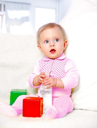 portrait of a cheerful little girl drinking water from a bottle on the abstract background Stock Photo - 17289457