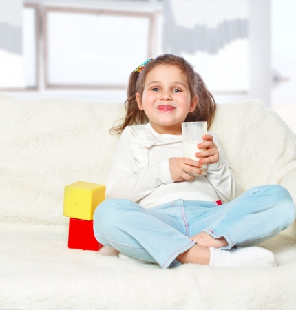 portrait of girl drinking milk and playing with blocks