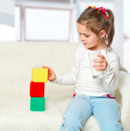 portrait of girl drinking milk and playing with blocks Stock Photo - 17289469