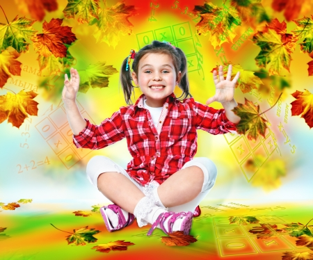 little girl schoolgirl sitting on the floor and smiling at an abstract background Stock Photo
