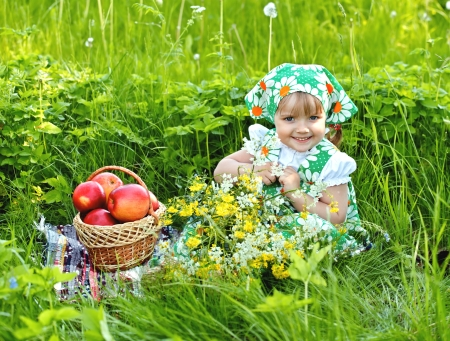 Baby girl is sitting on a glade and eating apples