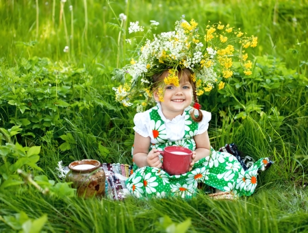 Baby girl is drinking milk sitting on a glade Stock Photo